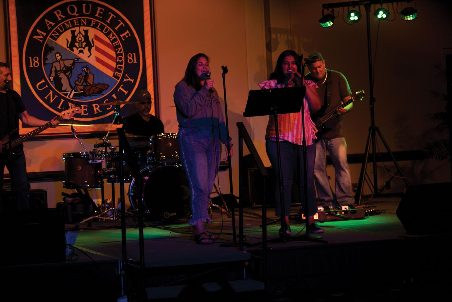 Students sing a duet onstage accompanied by a live band.
