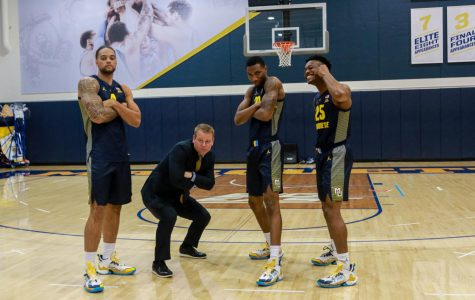 Junior forward Theo John (4), junior forward Jamal Cain (23) and redshirt junior guard Koby McEwen pose with head coach Steve Wojciechowski.