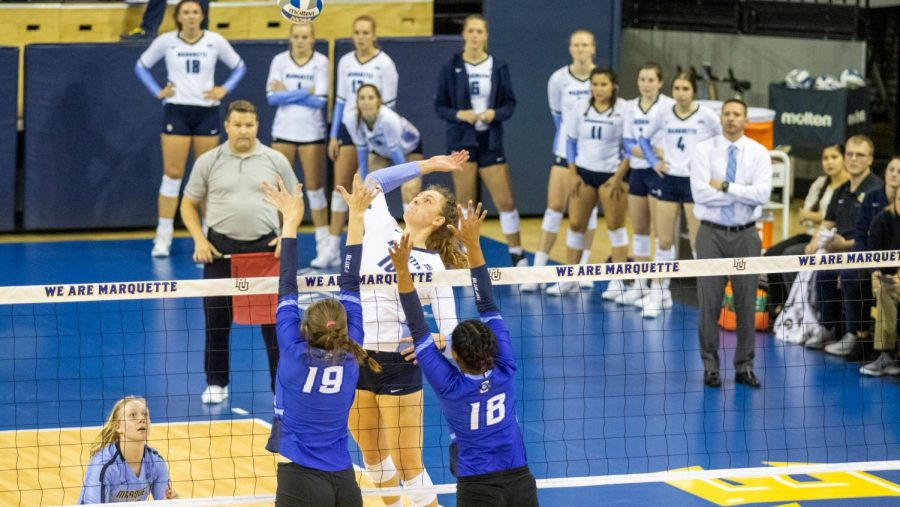 Senior outside hitter Allie Barber attempts a kill with her teammates watching.