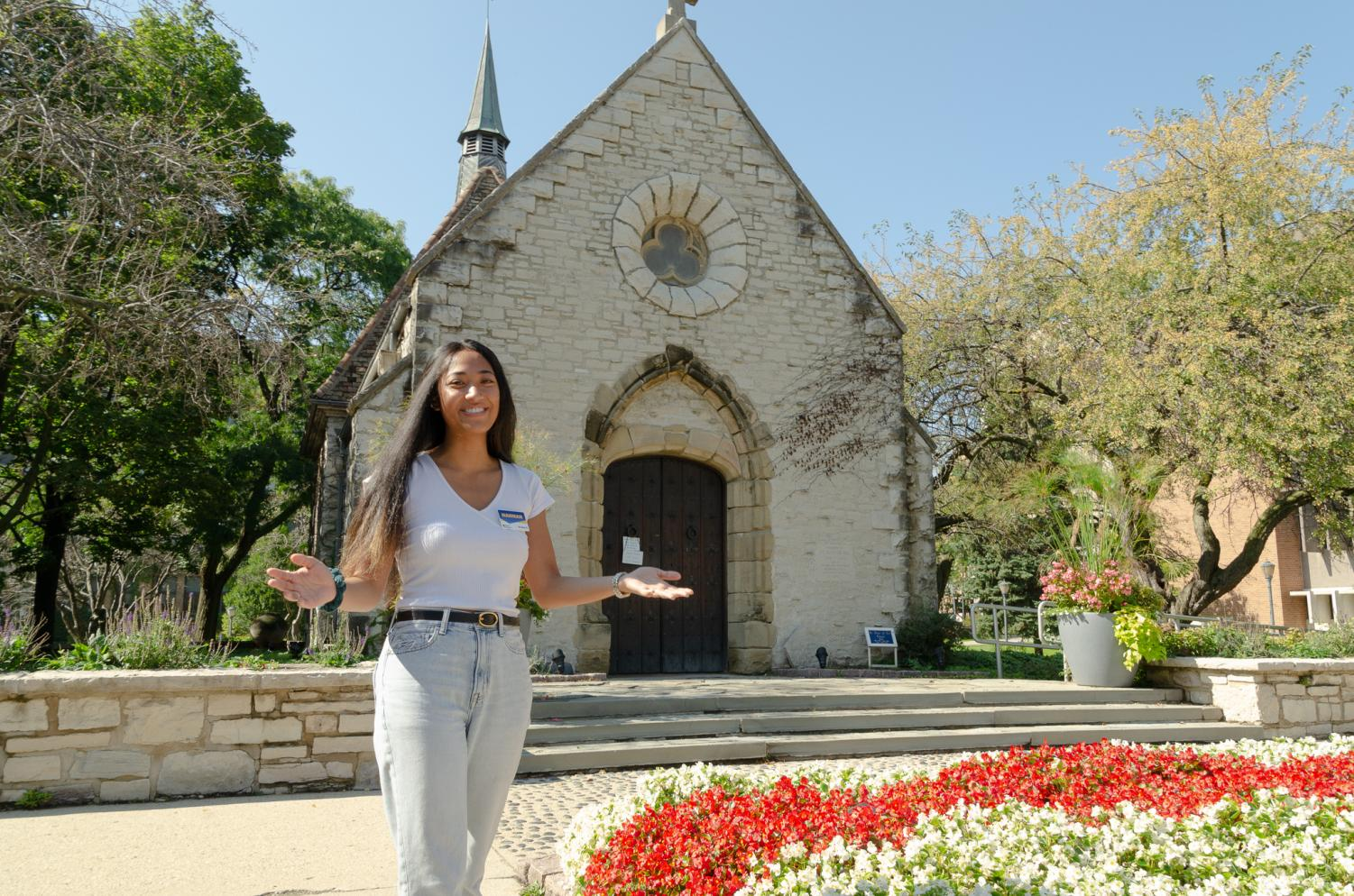 Hannah Quijano is a tour guide on campus. She leads a group to the St. Joan of Arc Chapel.