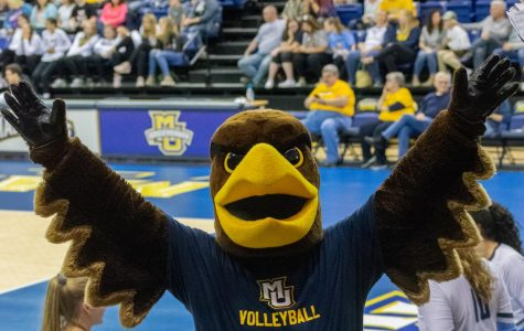 The mascot cheers at a women's volleyball game.