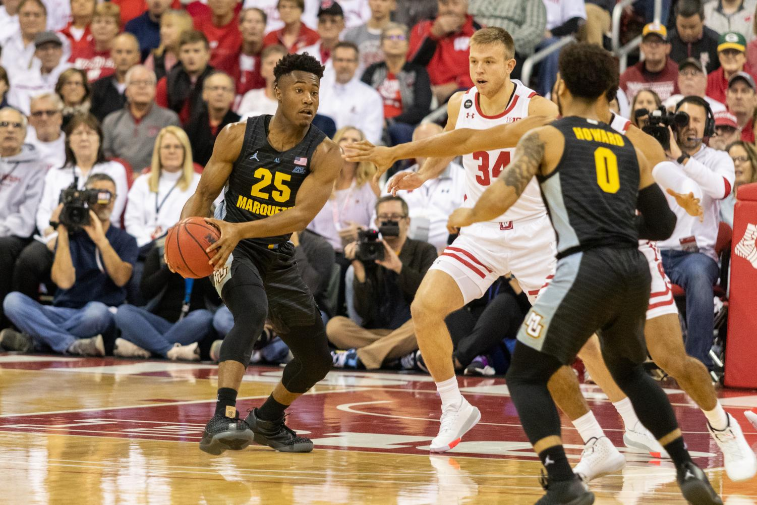 Redshirt junior guard Koby McEwen (25) passes the ball to teammate and senior guard Markus Howard (0) in MU's 77-61 loss to Wisconsin Nov. 17 at the Kohl Center in Madison.