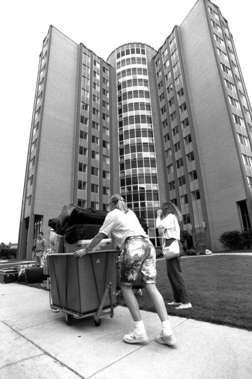 Students push bins to the entrance of McCormick Hall.