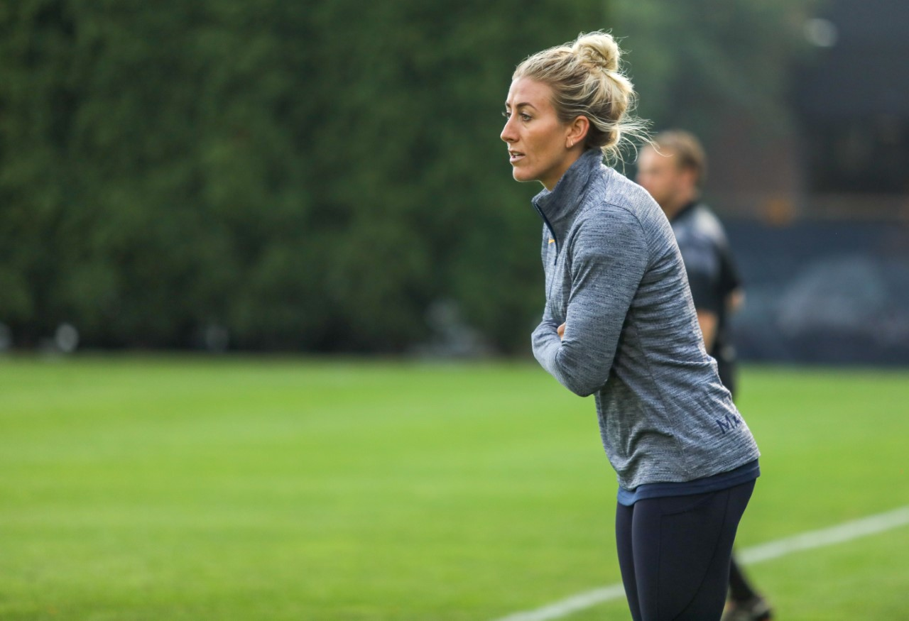 Assistant women's soccer coach Ashley Bares watches from the sidelines.