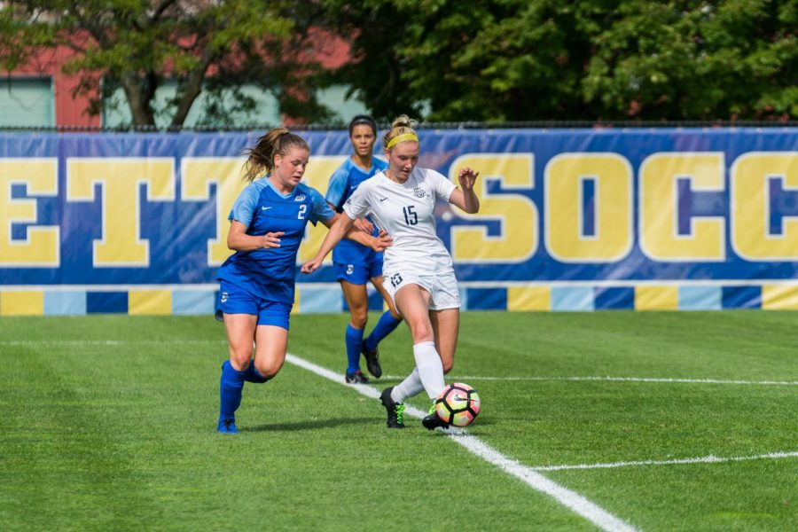 Alyssa Bombacino (15) dribbles the ball away from Creighton defenders.