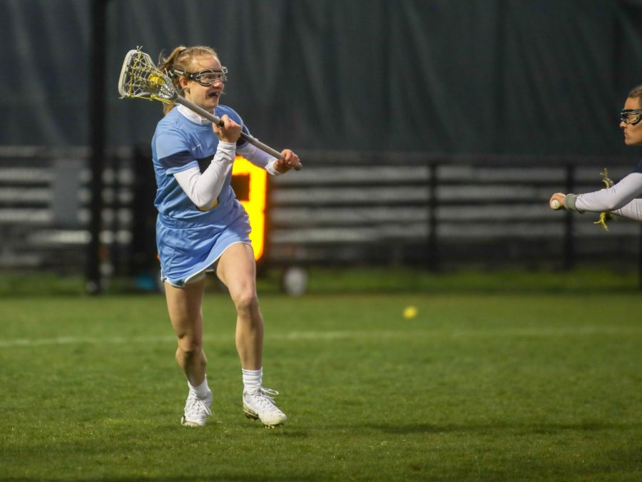 Megan Menzuber cradles the ball in the head of her lacrosse stick. (Photo courtesy of Marquette Athletics.)