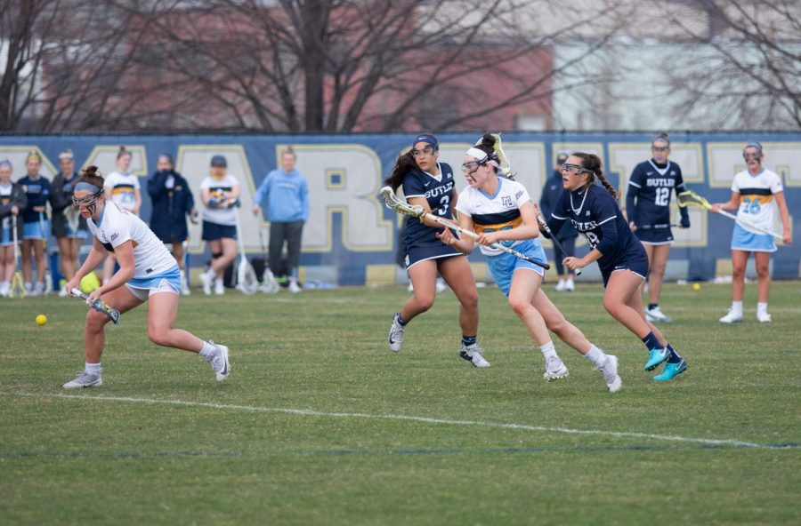 Grace Gabriel (left) goes to scoop the ball in Marquette's 14-12 win over Georgetown on April 27 2019.