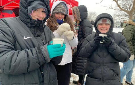 Students from Alpha Omega Epsilon are bundled up in the cold weather to help at the Milwaukee Cocoa Classic 5K event.