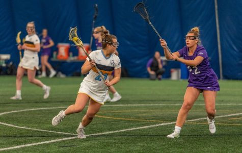 Shea Garcia (21) goes into the cage to score in Marquette's 16-6 win against Niagara on Feb. 23.