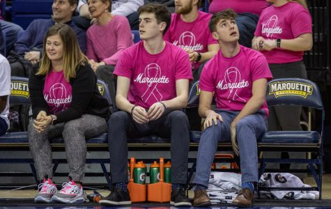 Women's basketball managers Quinn Faeth (center) and Mikey Garven (right) sit on the bench during Marquette's 76-54 win against Butler on Feb. 16.