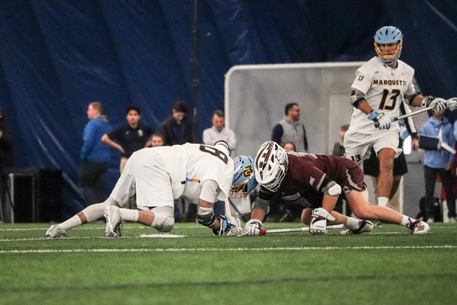 Marquette lacrosse player battles for ball against Bellarmine