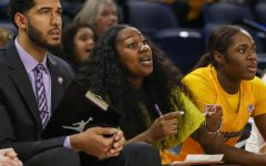 Vernette Skeete (center) coaches from the sidelines next to Scott Merritt (left) at the 2020 BIG EAST Women's Basketball Tournament in Wintrust Arena. (Photo courtesy of Marquette Athletics.)
