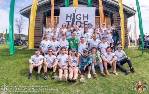 """Bryan Geenen (middle with green shirt) takes a photo  March 10 as a member of the men's and women's club ultimate frisbee teams. The teams were at a tournament called """"High Tide"""