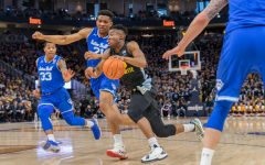 Koby McEwen (25) dribbles the basketball in Marquette's loss to Seton Hall Feb. 29 on Senior Day.