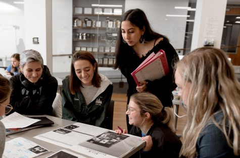 Skyler Daley, Kelli Arseneau, Jenny Whidden, Emma Brauer and Emily Rouse (from left) look over the Arts & Entertainment section of the Marquette Tribune during a production day in fall 2019. Photo courtesy of the Marquette Office of Marketing and Communications.