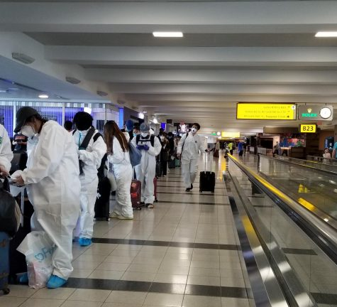 People in the airport wear protective equipment.   Photo courtesy of Henry Yang