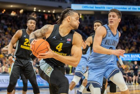Theo John (4) looks to make a play as Villanova guard Collin Gillespie closes in.