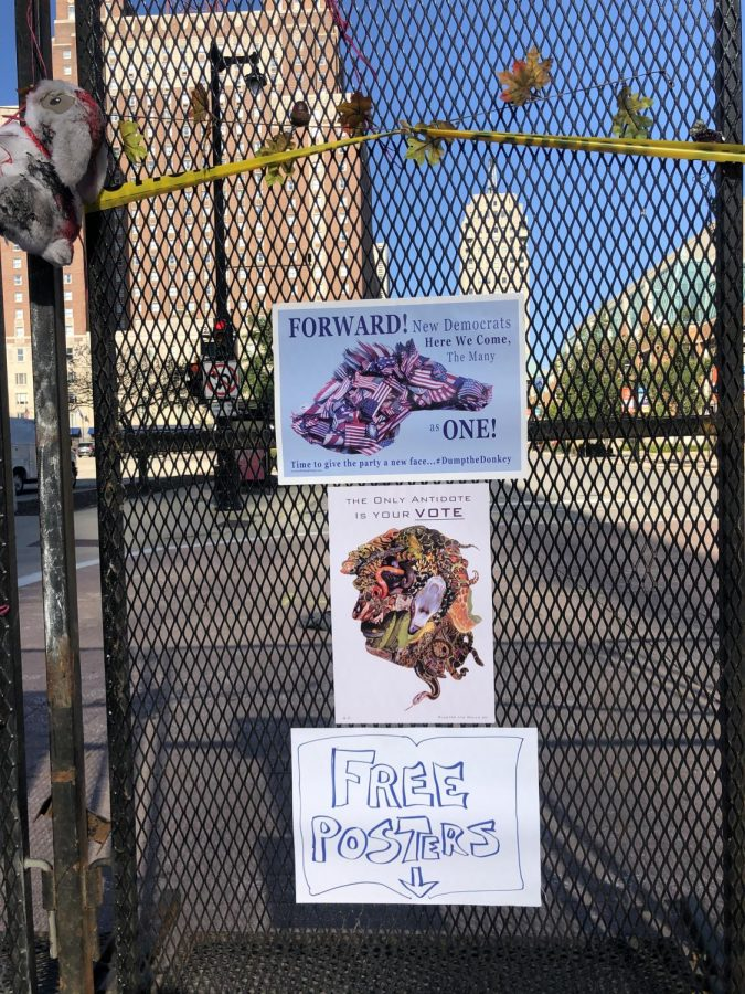 Smaller posters are hung on the fence outside of the Wisconsin Center.