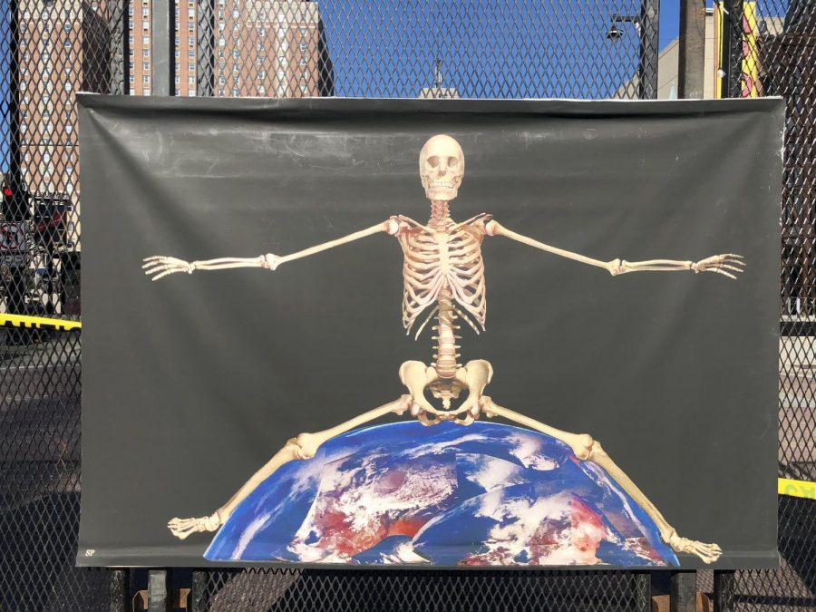 A skeleton sits on top of the world. The poster is placed on a barrier outside of the Wisconsin Center during the week of the DNC.