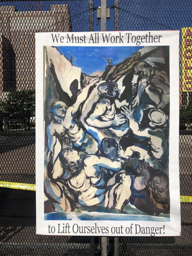A sign encouraging everyone to work together is tacked on the fence outside of the Wisconsin Center.
