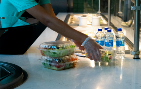 Dining hall staff prepare pre-packaged meals for students to grab-and-go.