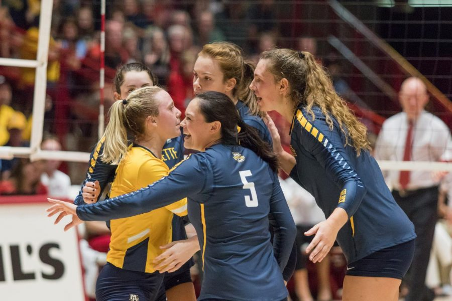 The volleyball squad huddled around setter Lauren Speckman (5) during a match at Wisconsin last season.