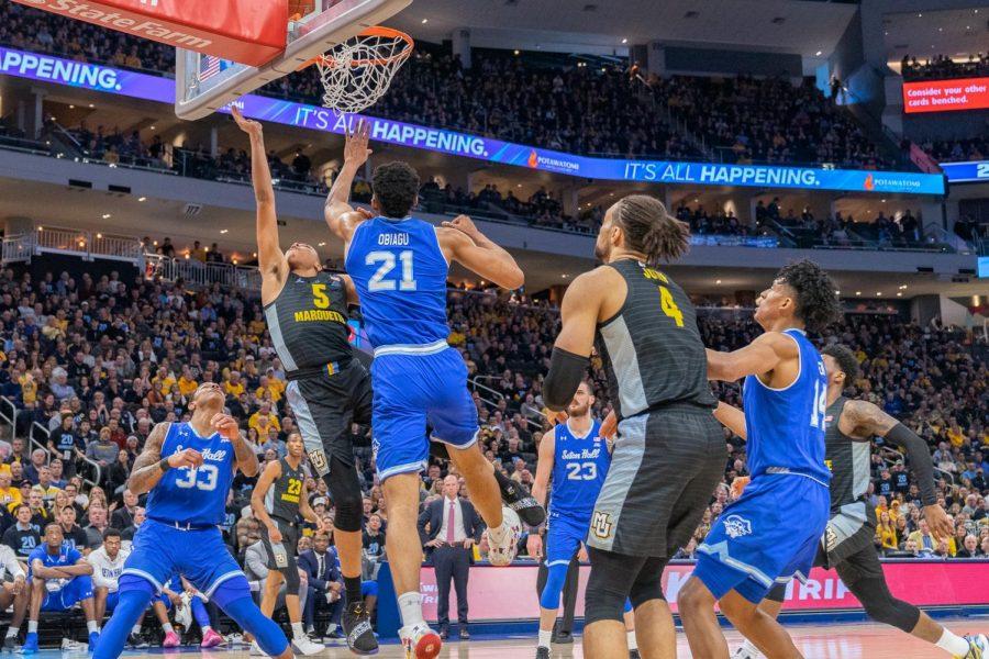 Greg Elliott (5) attempts a shot over Seton Hall's  Sandro Mamukelashvili in Marquette men's basketball Senior Day loss March 3.