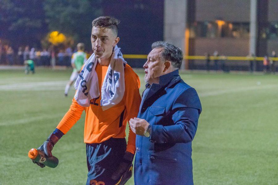 Goalkeeper Jackson Weyman speaks with men's soccer head coach Louis Bennett.