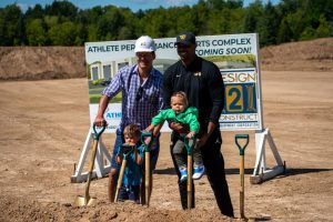 Former Marquette basketball alums Travis Diener (left) and Joe Chapman (right) pose with their children at the groundbreaking of the Athlete Performance Sports Complex Sept. 4.