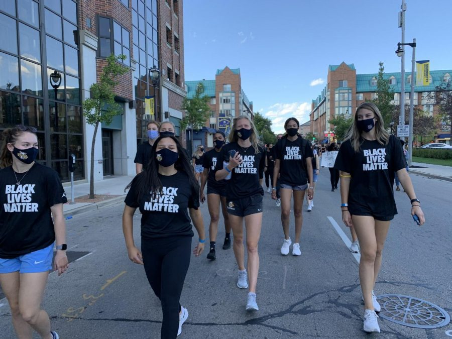 Carsen Murray (second from right) walks with the volleyball team in the athletes march Sept. 4. (Photo courtesy of Marquette Athletics.)