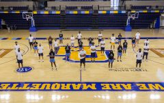 The Marquette men's and women's basketball teams stand together on the Al McGuire Center court Aug. 27. (Photo courtesy of Marquette Athletics.)