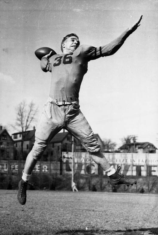 Marquette football player Ray Buivid jumps to throw a pass in 1936.