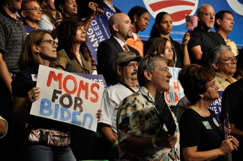 Biden supporters stand together holding signs.  Photo via Flickr