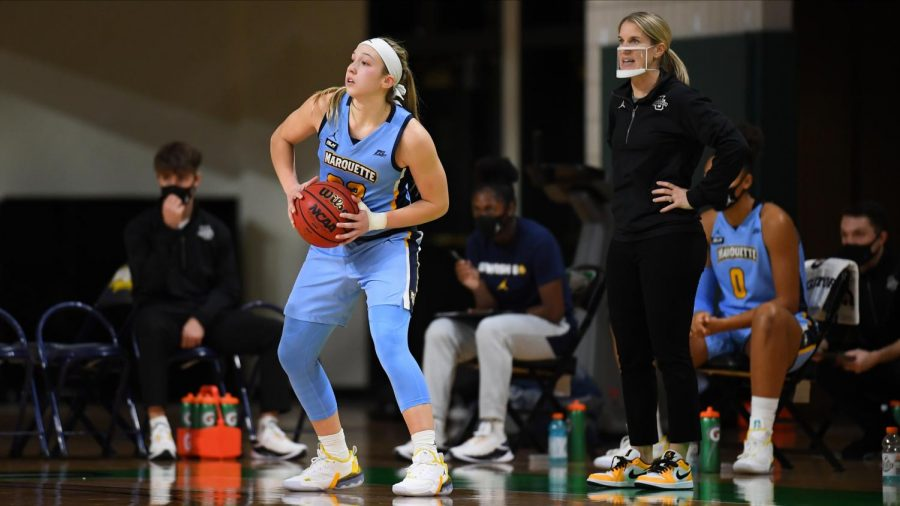 Jordan King (23) looks for a teammate, while Megan Duffy coaches from the sidelines in Marquette women's basketball's first win of the 2020-21 season. (Photo courtesy of Marquette Athletics.)