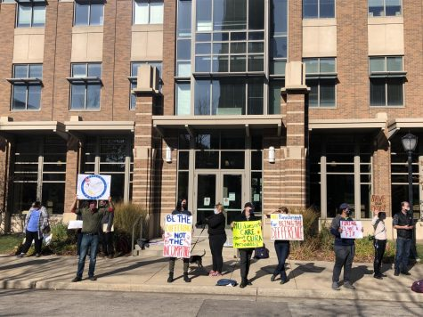 Protesters stand outside of Zilber while McArdle