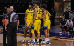 Justin Lewis (2) and Dawson Garcia (33) huddle with teammates during Tuesday's game against Oklahoma State (Photo courtesy of Marquette Athletics).