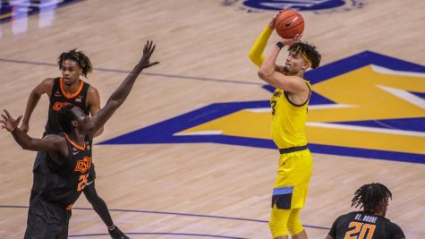 First-year forward Dawson Garcia attempts a shot over Oklahoma State sophomore forward Bernard Kouma (25) (Photo courtesy of Marquette Athletics).
