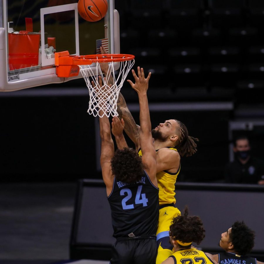 Senior forward Theo John puts up a shot over sophomore forward Jeremiah Robinson-Earl (24) (Photo courtesy of Marquette Athletics.)