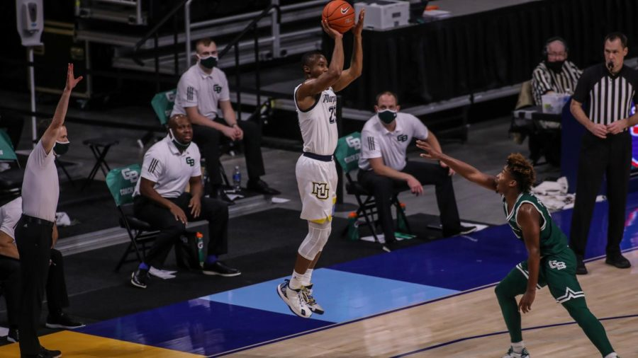 Redshirt senior Koby McEwen (25) shoots a jump shot over Green Bay's PJ Pipes. (Photo courtesy of Marquette Athletics.)