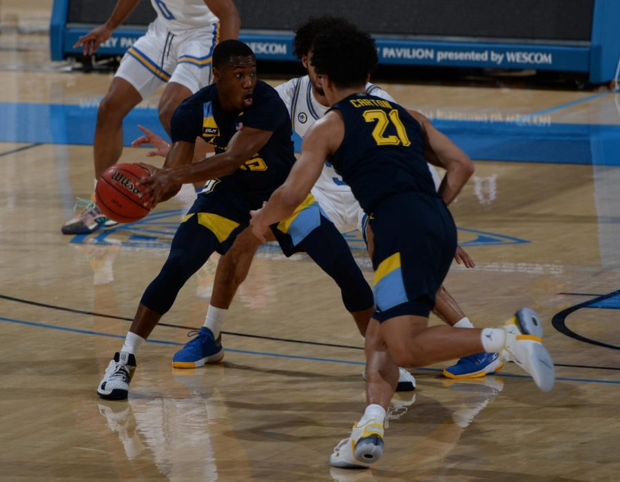 Redshirt senior guard Koby McEwen (25) looks to make a play as sophomore guard D.J. Carton (21) cuts by (Photo courtesy of Marquette Athletics.)