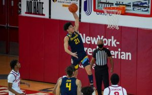 Sophomore guard D.J. Carton (21) dunks the ball against St. John's on Jan. 16. Carton had 14 points, nine of which came in the second half (Photo courtesy of Marquette Athletics.)