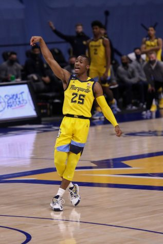 Redshirt senior guard Koby McEwen (25) watches his shot after shooting a three (Photo courtesy of Marquette Athletics.)