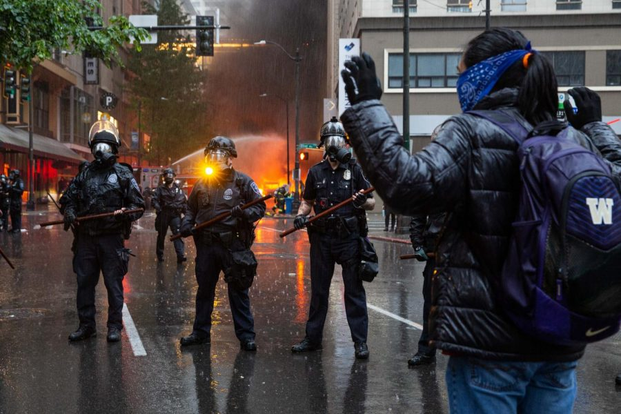 An individual stands in front of armed police officers during a Black Lives Matter protest in Seattle, Washington May 2020. Photo via Flickr