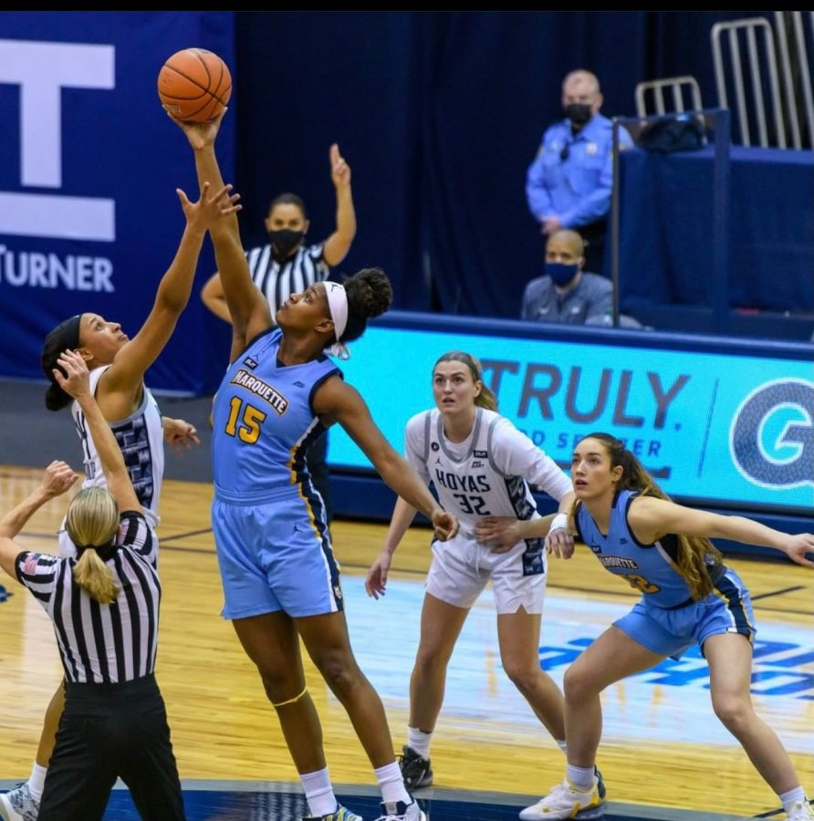 Camryn Taylor (15) reaches for the tip against Georgetown Wednesday. (Photo courtesy of Marquette Athletics.)