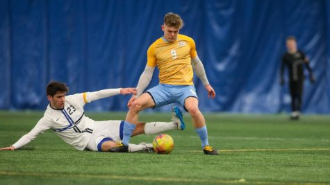 Junior forward Lukas Sunesson (9) shakes off a slide tackle (Photo courtesy of Marquette Athletics.)