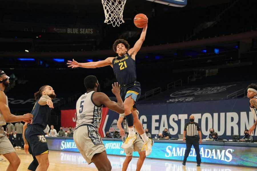 Sophomore guard D.J. Carton (21) throws down an aggressive dunk in the first half of the team's first-round matchup against Georgetown on Wednesday afternoon (Photo courtesy of Marquette Athletics.)