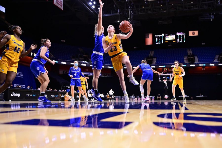 Jordan King (23) goes in for a layup against Creighton defense Sunday evening. (Photo courtesy of Marquette Athletics.)