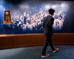 Shaka Smart during his tour of Marquette's campus March 28 looking at the NCAA 1977 championship trophy. (Photo courtesy of Marquette Athletics.)
