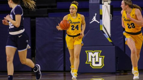Selena Lott (24) brings up the ball in Marquette