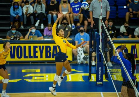 Carsen Murray (12) goes up for a kill in Marquette